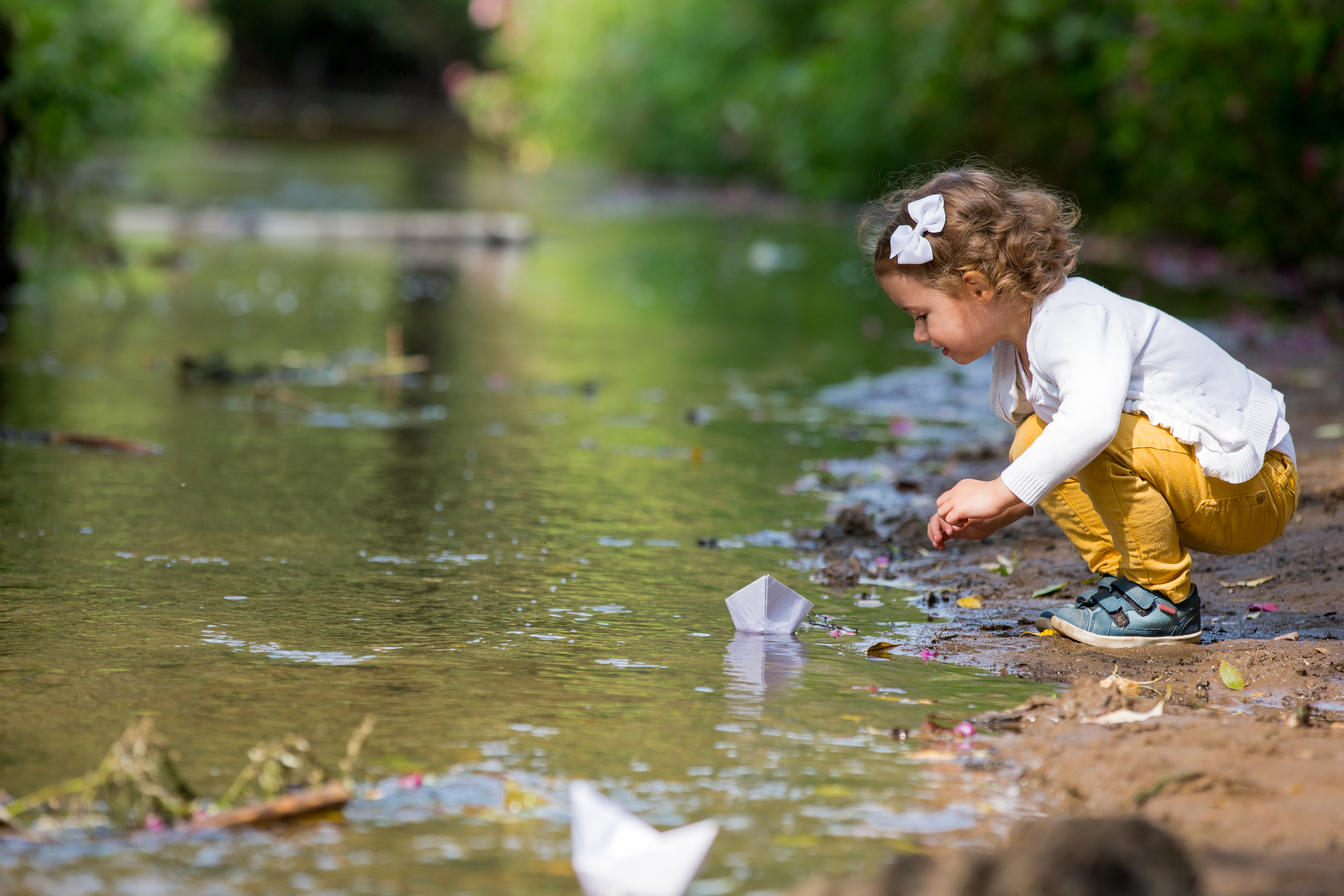 small girl reaching into creek water